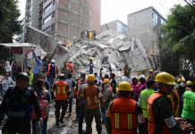 """Wie ein Kartenhaus eingestürzt ist dieses mehrstöckige Gebäude in der Hauptstadt. Helfer suchen teilweise mit Händen nach Verschütteten.oben: Feuerwehrleute, Polizisten, Soldaten und Freiwillige waren im Einsatz, um in Mexiko-Stadt in eingestürzten Gebäuden nach Überlebenden zu suchen.""""Silencio"""" — Ruhe, bitte! — Helfer, die nach Vermissten suchten, hofften, Geräusche unter den Trümmern zu hören."""