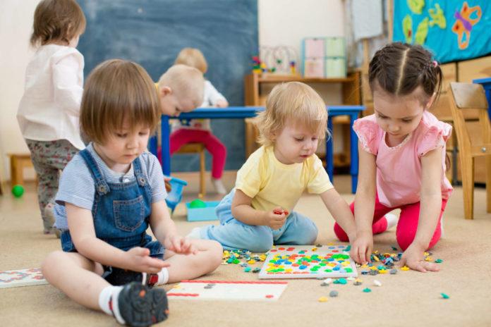 kids or children playing mosaic game in kindergarten room