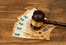 Judge gavel and money stack on wooden table.