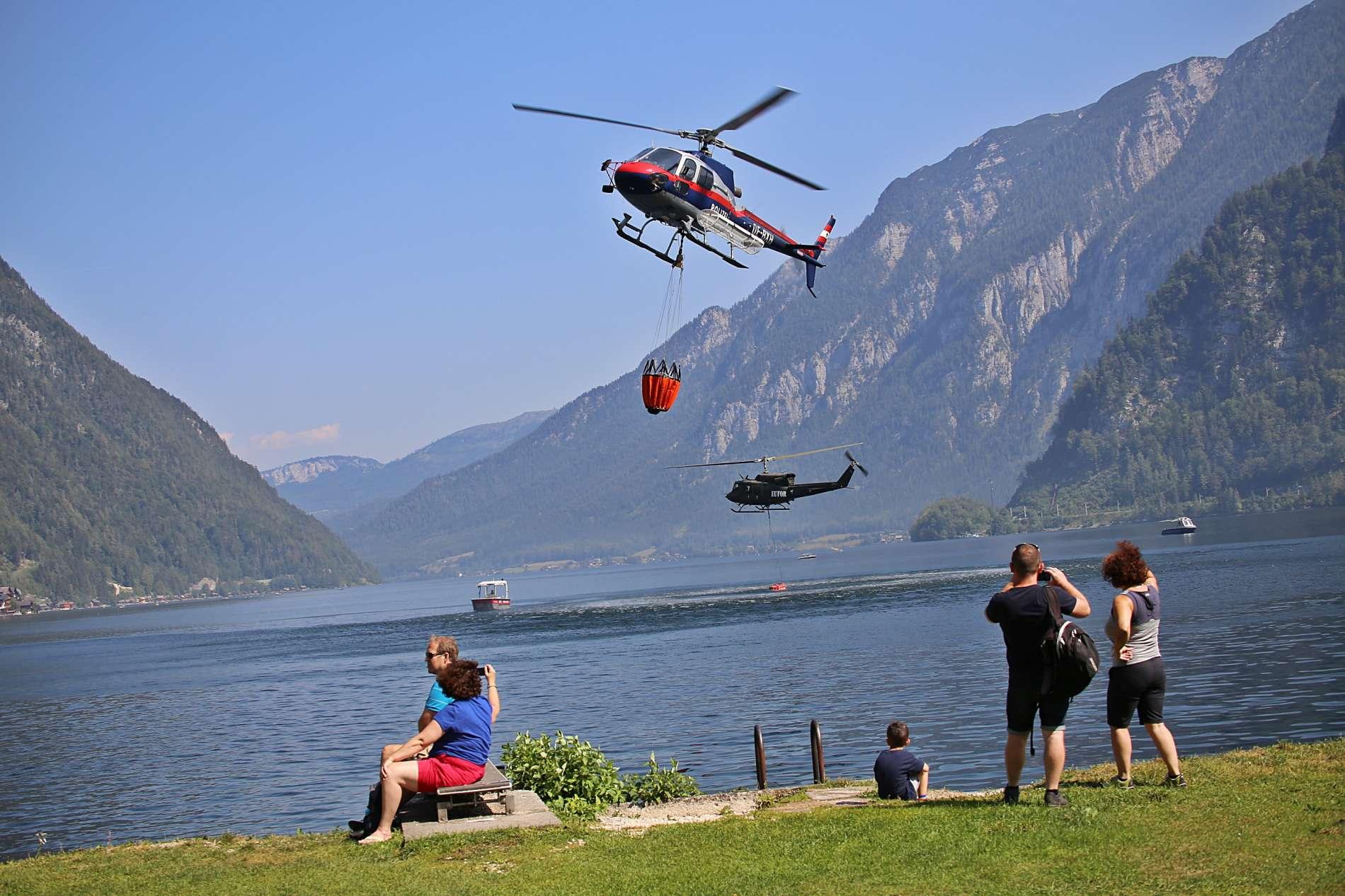 Mit Hubschraubern von Bundesheer und Innenministerium wird das Löschwasser vom See an den Brandort gebracht. Das Bild rechts lässt das Ausmaß des Brandes erahnen.