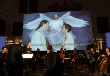 Michi Gaigg mit Ensemble vor einer Videoprojektion