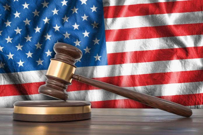 Wooden gavel and flag of USA on background - law concept
