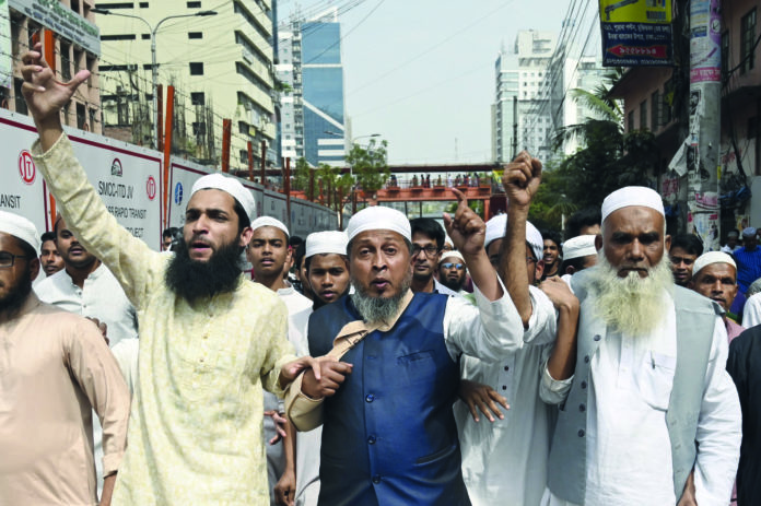 Oben: Ein Todesopfer am Gehsteig vor der Moschee.Rechts: Der mutmaßliche Haupttäter filmte die Bluttat und präsentierte sich im Internet.Links: In der islamischen Welt (hier Bangladesch) gehen die Wogen hoch.