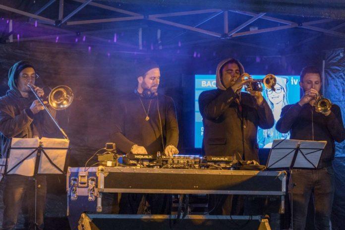 """DJ Pete Sabo flankiert von den """"Beat Horns""""."""