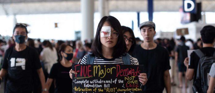 Demonstrantin mit Augenklappe, die daran erinnert, dass eine Frau bei einer Polizeiaktion das Augenlicht verlor.