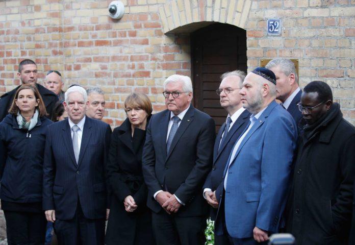 """""""Ein Tag der Scham und der Schande"""": Bundespräsident Steinmeier (2. v. l.) vor der Synagoge, deren Eingangstür die jüdische Gemeinde vor einem Massaker bewahrt hat."""