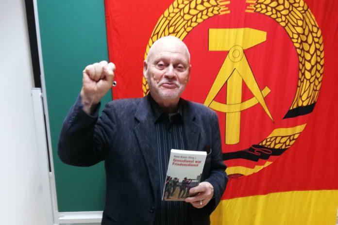 """""""Wir schaffen das!"""": Hans Bauer mit geballter Kommunistenfaust vor der DDR-Fahne mit seinem Buch """"Grenzdienst war Friedensdienst"""" im Volkshaus Linz-Pichling."""