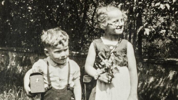Angela Leimer mit ihrem Bruder, der den Behälter mit dem Fotoapparat eines Wehrmachtssoldaten in den Händen hält.