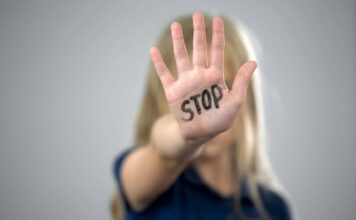 Little girl showing stop sign, child abuse issue, cruelty in