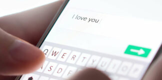 Sending I love you text message with mobile phone. Online da