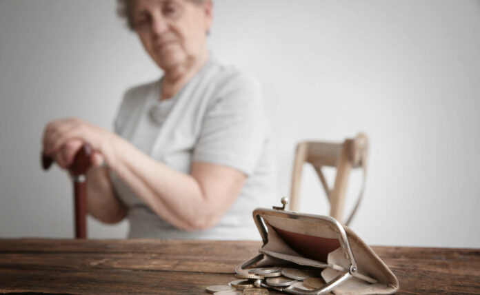 Purse with coins and blurred senior woman on background. Pov