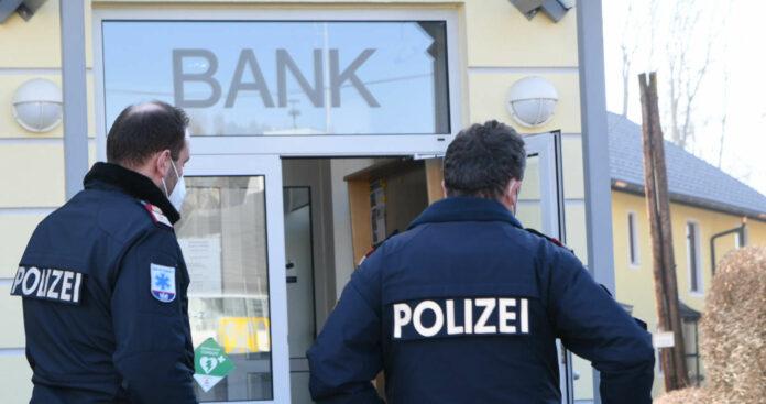Polizisten vor der Innviertler Bank, von wo aus der Täter zu Fuß die Flucht ergriffen hat.