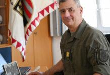 Im Büro von Kommandant Brigadier Dieter Muhr steht vor dem Computer ein Foto mit der Familie, dahinter hängt die Fahne vom Militärkommando Oberösterreich.