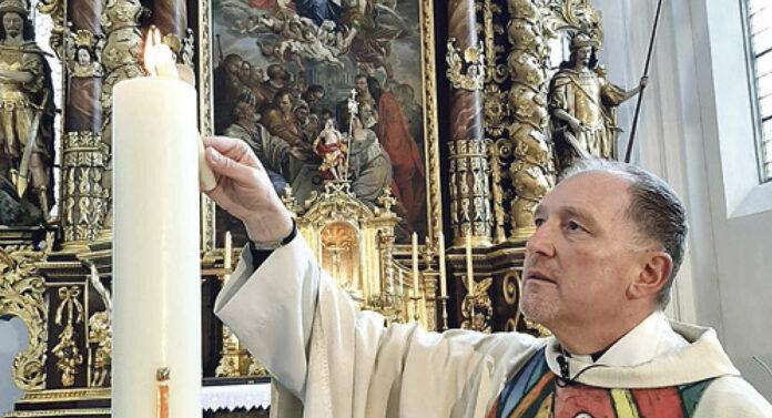 Pfarrer Wolfgang Schnölzer aus Vöcklamarkt entzündete zu Ostern 2020 im Alleingang die Osterkerze als ein leuchtendes Symbol der Auferstehung Jesu.