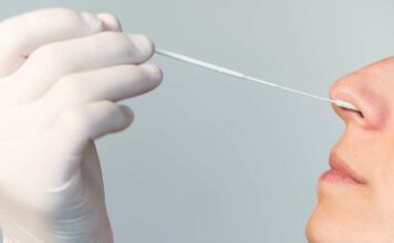 A nurse wearing latex gloves inserts a swab into a woman's n
