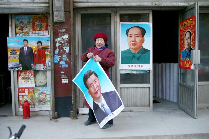 """Eine Ladenbesitzerin in der chinesischen Stadt Gaobeidian: Zu Neujahr Poster des """"Überragenden Führers"""" Xi Jinping auf Augenhöhe mit Übervater Mao."""