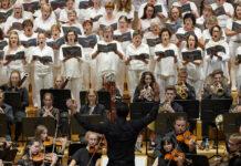 Sängerinnen und Sänger in Weiß auf der Bühne des Linzer Brucknerhauses.